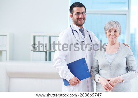 Smiling doctor with clipboard and elderly female patient in clinic - stock photo