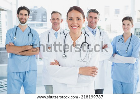 Smiling doctor with fellow doctors standing behind her - stock photo