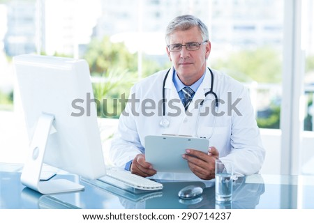 Smiling doctor working on computer at his desk in medical office - stock photo