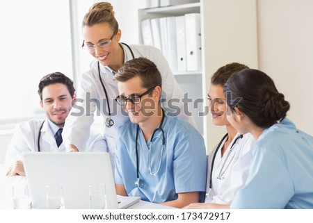 Smiling doctors and nurses discussing over laptop in hospital - stock photo
