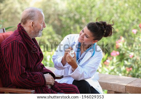 smiling Dr or nurse giving medication to senior patient.  - stock photo