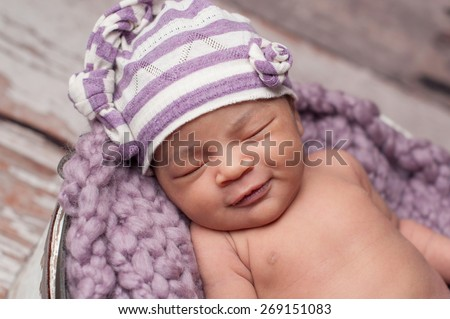 Smiling eight day old newborn baby girl wearing a striped lilac and white upcycled sleeping cap. She is sleeping on a lilac colored knitted blanket. - stock photo