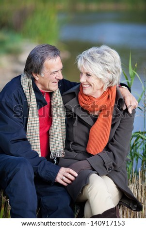 Smiling elderly couple on a lake shore sitting on a rock looking into each others eyes with love and affection - stock photo