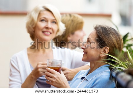 Smiling elderly female colleagues having lunch break at patio and drinking tea - stock photo