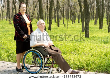 Smiling elderly man with one leg amputated sitting in his wheelchair in a wooded park attended by his wife or carer - stock photo