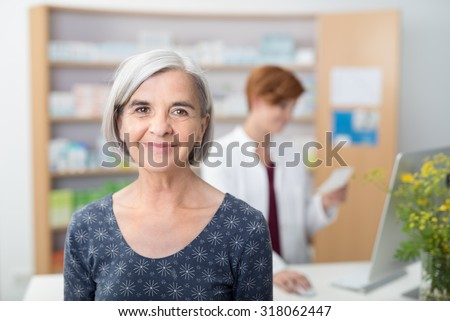 Smiling elderly patient in a pharmacy, head and shoulder facing the camera with a young female pharmacist working in the background - stock photo