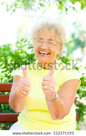 smiling elderly woman holding her thumb up outdoors  - stock photo
