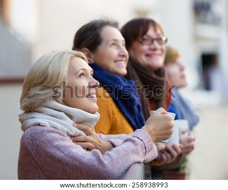 Smiling elderly woman in warm clothes having cup of hot tea on terrace. Focus on blonde woman - stock photo