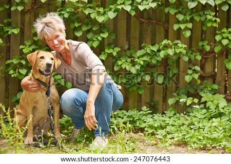 Smiling elderly woman sitting with a dog in a garden in summer - stock photo