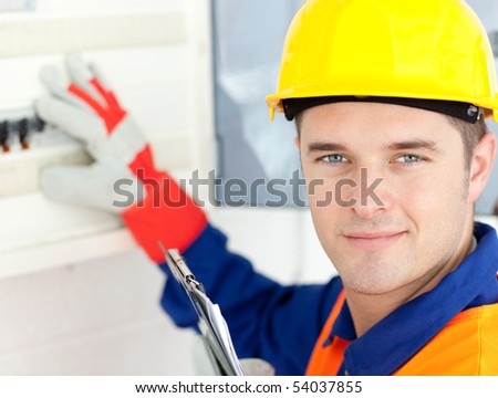 Smiling electrician repairing a power plan at work - stock photo