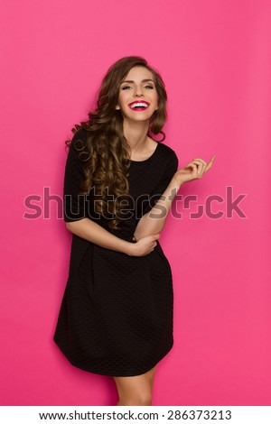Smiling elegance woman in classic black mini dress. Three quarter length studio shot on pink background. - stock photo