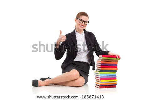 Smiling elegance woman sitting on the floor close to stack of books and showing thumb up. Full length studio shot isolated on white. - stock photo