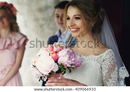 Smiling elegant blonde bride with rose wedding bouquet in white dress and veil - stock photo