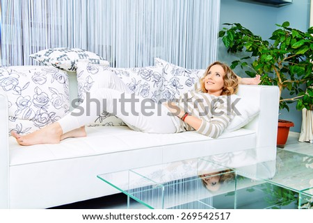 Smiling elegant woman lying on a sofa in a living room. Home interior, furniture. Lifestyle. - stock photo