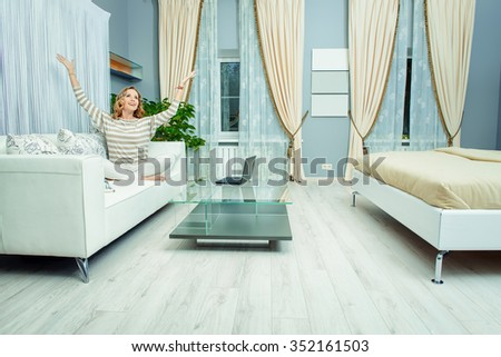 Smiling elegant woman sitting on a sofa in a bedroom. Home interior, furniture. Lifestyle. - stock photo