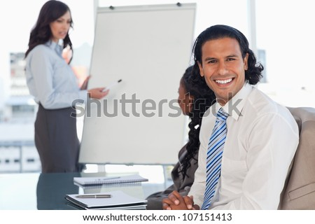 Smiling employee attending a presentation while his team is working behind him - stock photo