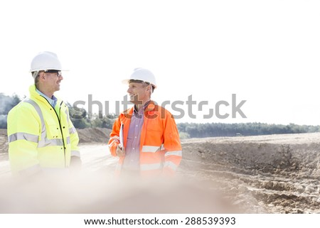 Smiling engineers discussing at construction site on sunny day - stock photo