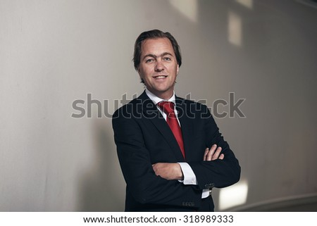 Smiling entrepreneur with red tie against white wall. - stock photo