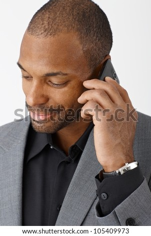 Smiling ethnic businessman concentrating on mobile phone call, closeup portrait. - stock photo