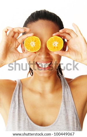 Smiling Eurasian woman holding slices of oranges to her eyes on white background - stock photo