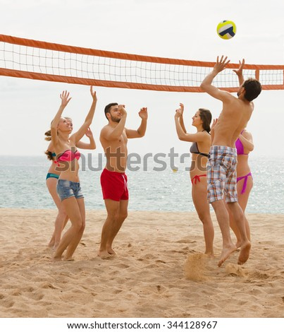 smiling European adults throwing ball over net and laughing   - stock photo