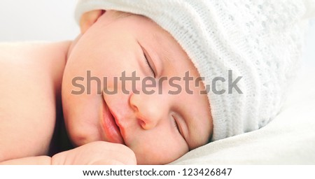 smiling european newborn baby in white hat - stock photo