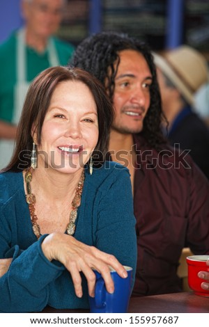 Smiling European woman with Latino man in cafe - stock photo