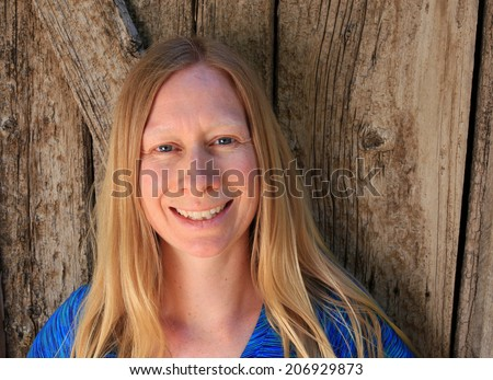 Smiling everyday woman with a barn wood background. - stock photo