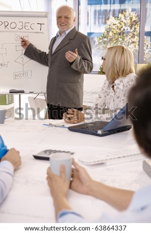 Smiling experienced businessman training employees using whiteboard in office.? - stock photo
