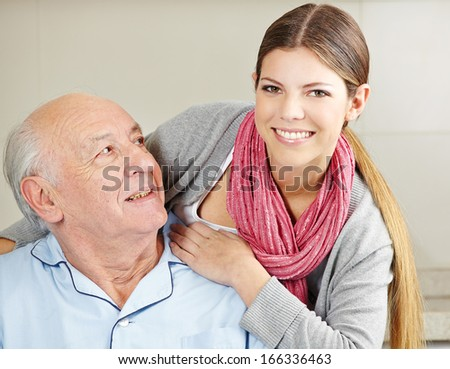 Smiling extended care assistant with happy senior citizen - stock photo