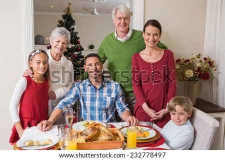Smiling extended family looking at camera at christmas time at home in the living room - stock photo