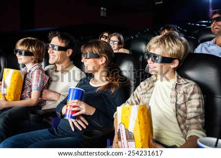 Smiling families with snacks watching 3D movie in cinema theater - stock photo