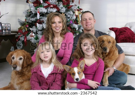 smiling family and dogs sitting by Christmas tree - stock photo
