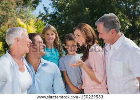 Smiling family and grandparents talking in the park together - stock photo
