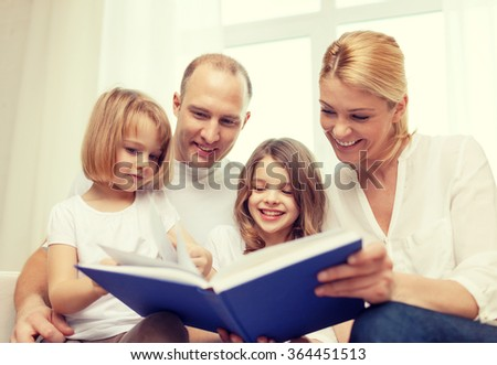 smiling family and two little girls with book - stock photo
