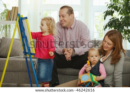 Smiling family at home little girl drawing on board. - stock photo