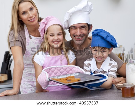 Smiling family baking cookies in the kitchen - stock photo