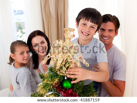 Smiling family decorating a Christmas tree at home - stock photo