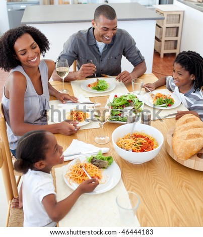 Smiling family dining together in the kitchen - stock photo