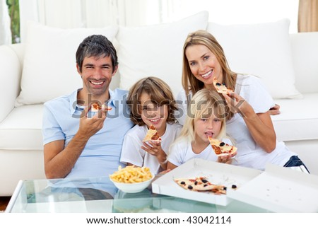 Smiling family eating a pizza sitting on the floor in the living-room - stock photo