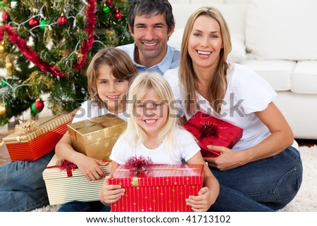 Smiling family holding Christmas presents in the living-room - stock photo