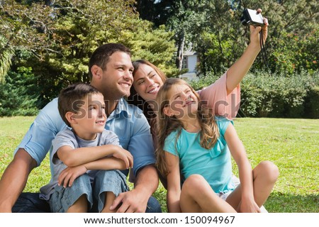 Smiling family in a park taking photos in the sunshine - stock photo