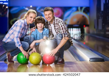 Smiling family in biwling club - stock photo