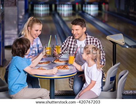 Smiling family in bowling cafe - stock photo