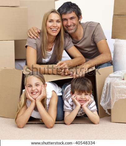 Smiling family in new house playing with boxes - stock photo