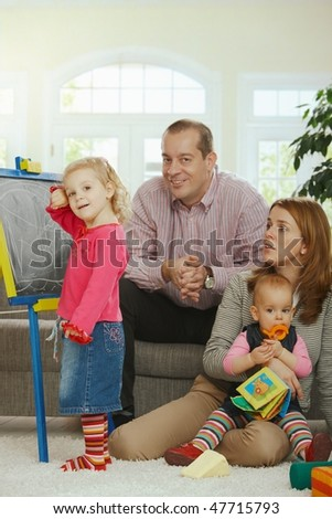 Smiling family looking at camera little girl drawing on board at home. - stock photo