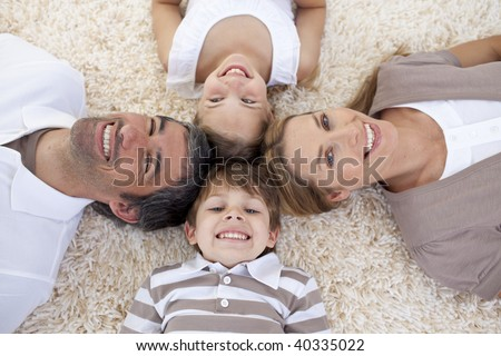 Smiling family lying on floor with heads together - stock photo