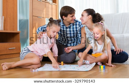Smiling family of four playing at board game in domestic interior - stock photo