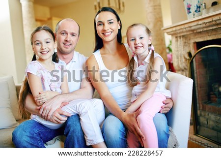 Smiling family of four sitting on sofa at home - stock photo