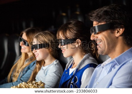 Smiling family of four watching 3D movie in cinema theater - stock photo